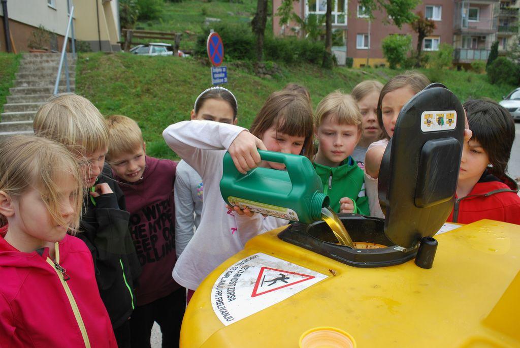 Tretješolci vedo, da odpadno jedilno olje zlijemo v rumeni zbiralnik. Foto: arhiv OŠ Kanal