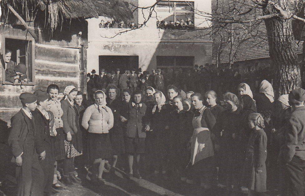 Gabrčani pred staro šolo; razpravljajo o ustavi, leto 1946, hrani Dolenjski muzej.