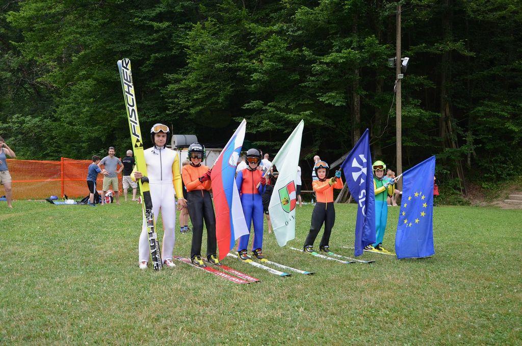 Slavnostni spusti članov po doskočiščih z zastavami in otvoritveni skok Davida Grma na skakalnici K 35