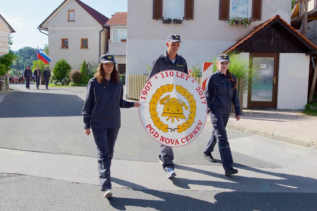 Čelo parade: gasilski znak jubilanta. Nosilci Jaka Legvart, Maruša Boršič, Martina Marovšek.