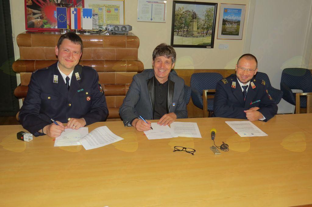 Predsednik PGD Bistrica pri Tržiču Luka Rener, župan Občine Tržič mag. Borut Sajovic in poveljnik PGD Bistrica pri Tržiču Aleš Meglič podpisujejo pogodbo o sofinanciranju (foto Media butik)