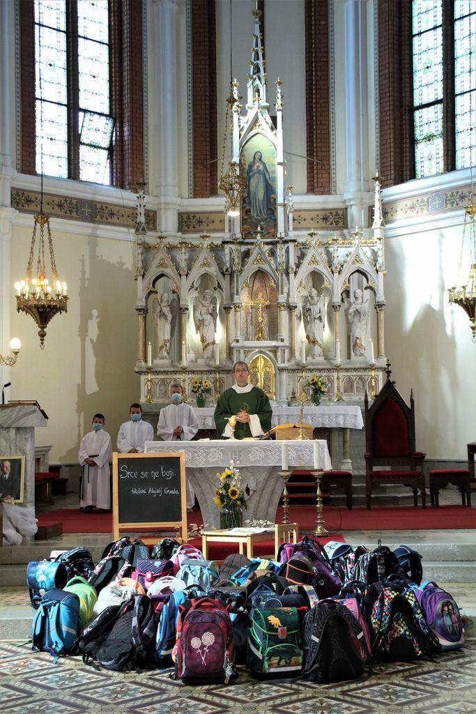 Šolske torbe pred oltarjem