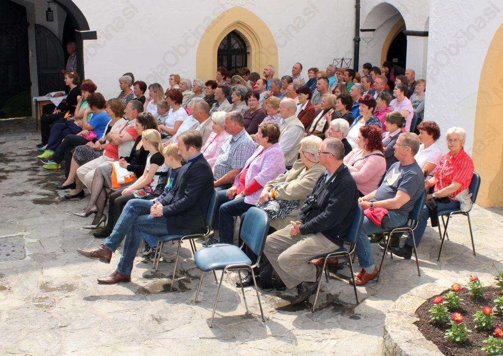 Obiskovalci koncerta v grajskem atriju