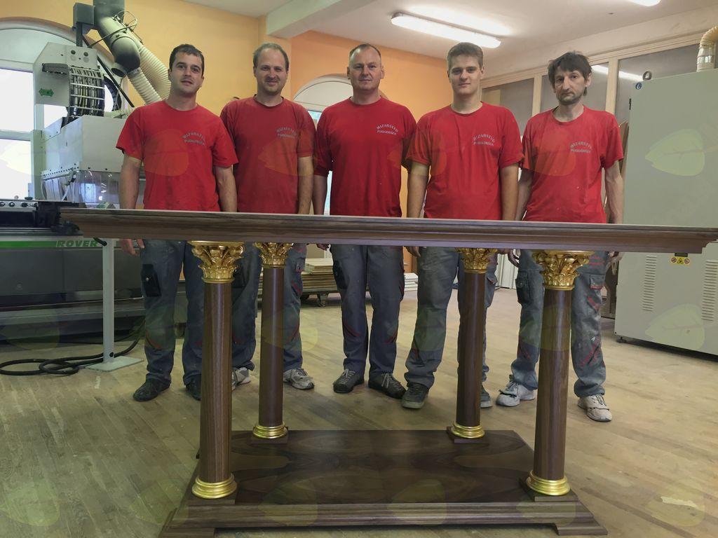 Delovni kolektiv ob svojem izdelku – oltarni mizi, ki stoji v farni cerkvi na Frankolovem.