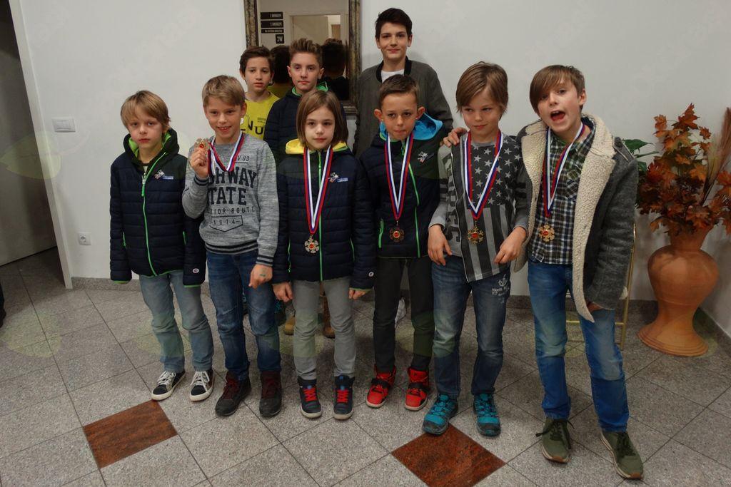 Mladi skakalci iz SSK Mengeš ovenčani s kolajnami in pokali.