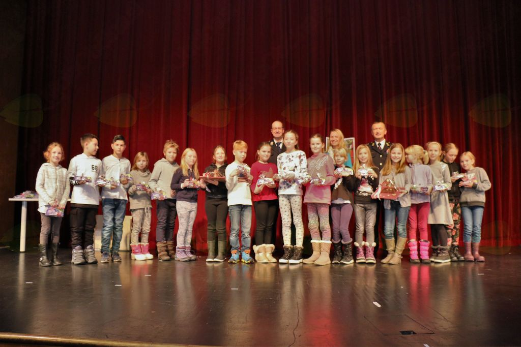 Skupinska fotografija nagrajencev, 4.a in 4.b razreda Osnovne šole Mengeš, z Robertom Ručigajem, predsednikom Komisije za mladino Gasilske zveze Mengeš, in Janezom Koncilijo, predsednikom Gasilske zveze Mengeš.