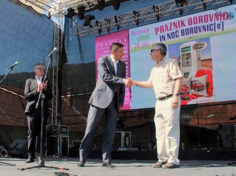 Predsednik Republike in ameriški veleposlanik se ob nazvočnosti župana rokujeta na odru Praznika borovnic 2017