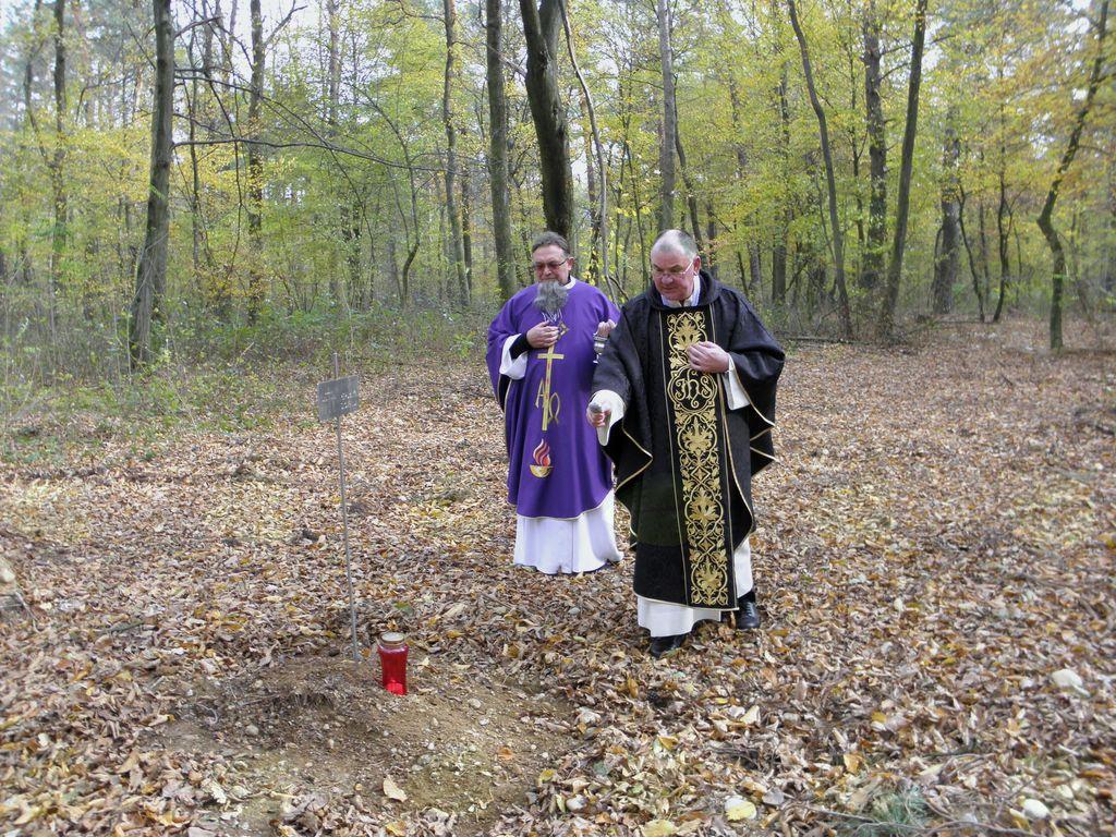 Župnika blagoslavljata grobove.