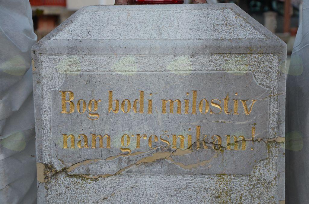 Vabeči in opozorilni napis na kamniti plošči