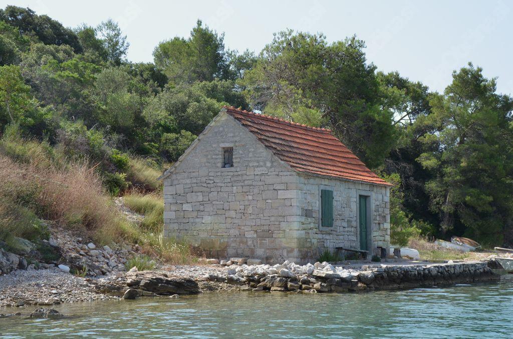 Zapuščena ribiška hišica ob obali.