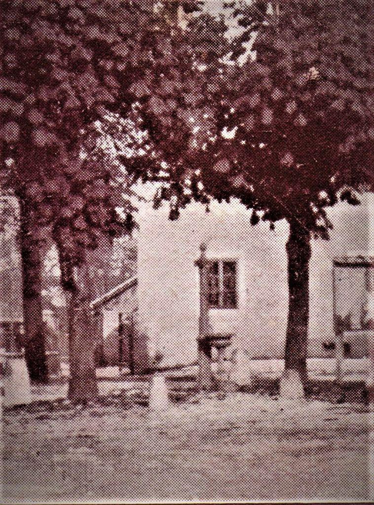 Izrez fotografije Dolnjega Logatca med Notranjsko cesto in Cankarjevo ulico z litoželeznim pitnikom poleg kapelice sv. Jožefa,1922 t. p. q., 1928 t. p. q. n. (Zbirka starih razglednic Knjižnice Logatec)