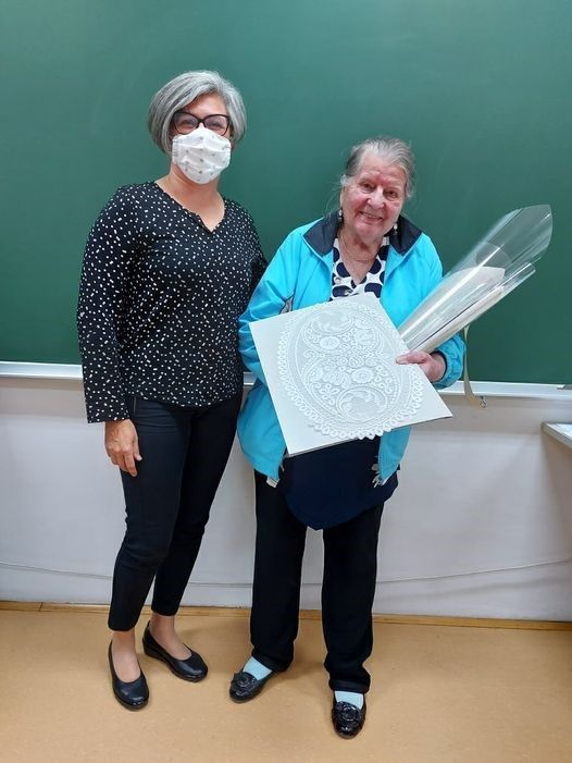 Naša učenka v programu čipkarske šole za odrasle, gospa Marjanca Yartz, je pravi primer vseživljenjskega učenja. Njene zlate roke klekljajo že dobrih osem desetletij. (Levo gospa Metka Fortuna, ravnateljica Čipkarske šole Idrija.) Foto Čipkarska šola Idrija.