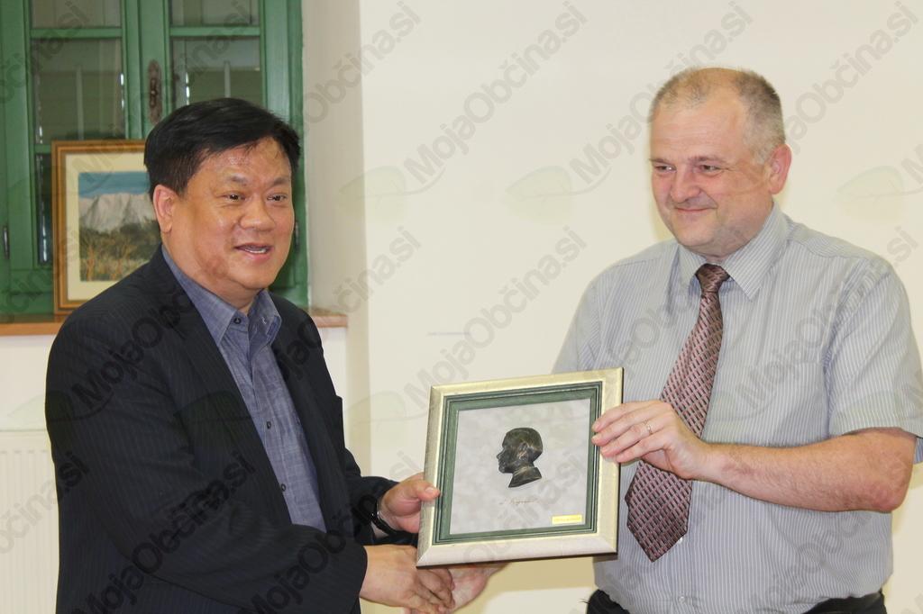 Dr. Georg So je iz rok župana Občine Kobarid prejel spominsko sliko Simona Gregorčiča. Foto: Nataša Hvala Ivančič