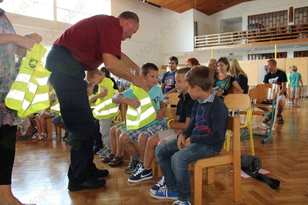 Prvošolčke je pozdravil tudi redar Janko Volarič, ki jih bo obiskoval in z njimi sodeloval celo šolsko leto. Predal jim je odsevne brezrokavnike in kape, s katerimi bodo v prometu vidni in varni ter jim zaželel varno pot v šolo! Foto: Nataša Hvala Ivančič