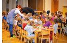 Vzgojiteljica Monika pomaga otrokom pri pripravi zajtrka