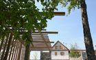 Potem: parkirišče senčeno z leseno pergolo, drevesi in trto