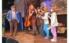 Povezovalca večera Barbara Rednak Robič in humorist Janez Cankar z briškimi otroki, ki so jo dobro zagodli.