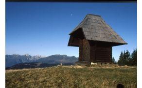Kapela sv. Cirila in Metoda pod vrhom Komna (1684 m), v ozadju sta Ojstrica (2350 m) in Raduha (2062 m). Foto l. 1999, Ciril Velkovrh.