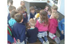 Otroci poslušajo sporočilo palčka Pozdravčka