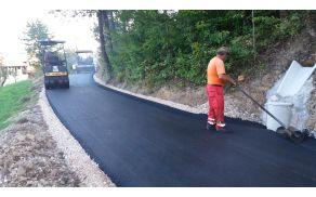 Polaganje asfalta na cesti v Bezenškovo Bukovje.