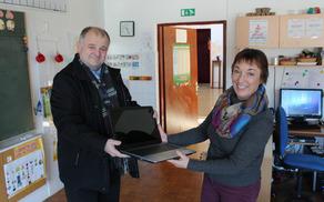 Župan Občine Kobarid Robert Kavčič je predal prenosni računalnik vodji POŠ Drežnica Rini Berginc. Foto: Nataša Hvala Ivančič