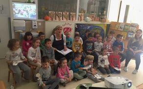 Otroci in vzgojiteljica, ki sodelujejo v projektu Pomahajmo v svet