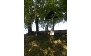 Juhartov križ, postavljen leta 1897 in v odzadju spomenik padlim borcem z leta 1979.