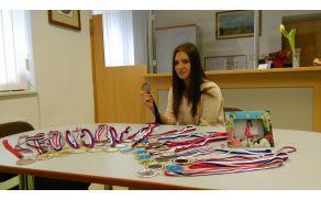 Uspešna tekmovalka v twirlingu Eva Mlakar in njene medalje (foto: Lidija Eler Jazbinšek)