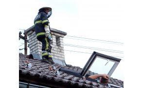 Čebelar na strehi? Ne, gasilec preganja sršene.