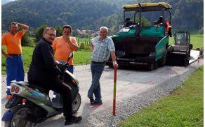 Nasmejani obrazi ob asfaltiranju ciljne ravnine pred Dražico. Na motorju predsednik vaškega odbora Karel Nikolavčič, skrajno desno vodja del Bojan Pelko.