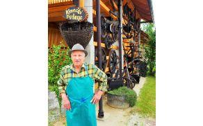 Ivan pri obnovljenem kozolcu s starim kmečkim orodjem