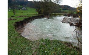 Močna zajeda vodotoka je poškodovala del kmetijskega zemljišča.