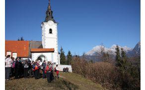 Skupinska pred cerkvijo z alpsko panoramo v ozadju
