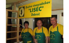 """Člani Društva vinogradnikov """"Lisec"""" Dobrnič ob stojnici - pripravljeni na točenje vina."""